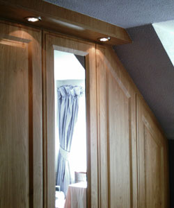 Fitted wardrobe showing fitting to roof features