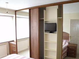 Mirrored wardrobe with shelf unit and television mounted in the shelf unit